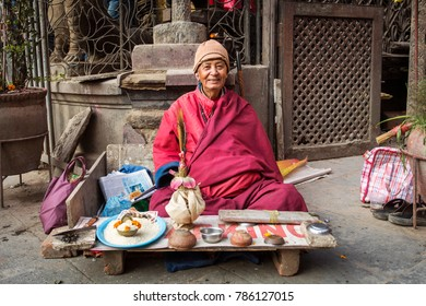 DURBAR SQUARE, KATHMANDU, NEPAL - NOVEMBER 10, 2017: Monk waiting for people to bless in a temple in Kathmandu, Nepal.
