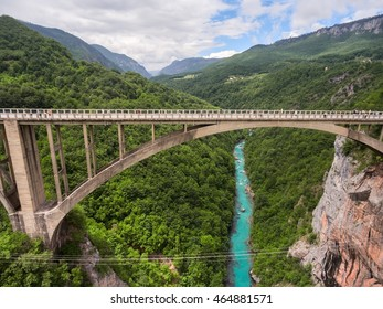 The Durdevica concrete arch bridge. Cars driving and people riding on zip-line. Tara River canyon, Montenegro. Aerial side view from flying drone