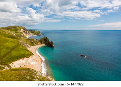 Durdle Door, Dorset tourism attraction view from west side. Sunny afternoon light with clouds on blue sky and azure sea.