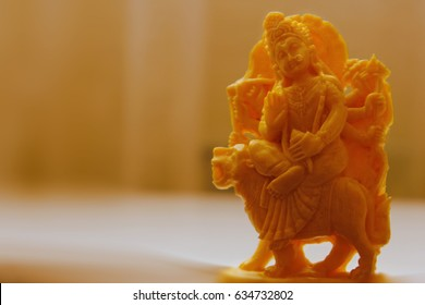 Durga devi is an Indian figurine made of natural bone on a yellow background.
