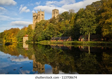 Durham Cathedral above the Old Fulling mill and boat houses reflected in the river wear in autumn colors.