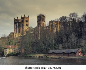 Durham Cathedral on an overcast day in late winter, showing the Fulling Mill in the foreground together with one of the River Wear's several boathouses.