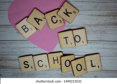 Durham, UK - 18 August 2019: Back to School concept. Back to school spelled out on scrabble letters on a rustic wooden background. Preparation for going back to school after the summer holidays.