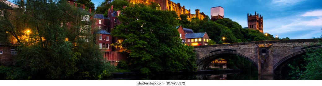 Durham, UK. Illuminated Castle and University in Durham, UK. Popular landmarks in the evening. Sunset with reflection in the river and historical bridge
