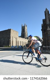 Durham,North Carolina/United States- 09/07/2018: A college student rides his bike across campus with Duke Chapel behind.