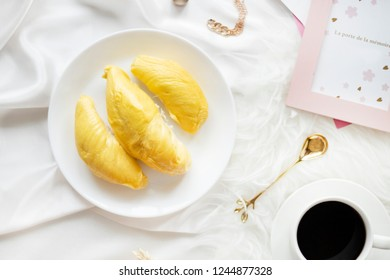 Durian Flatlay on White Background. Durian with Coffee on a White Table. Top Down View of Durian with Gold Spoon and Coffee. Translation on the frame: The Door to Memory