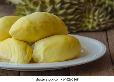 Durian the king of fruit in Thailand on white plate put on rustic wood table. One of popular tropical Thai traditional fruits so delicious, sweet and good smell. Ripe durian has yellow gold color.