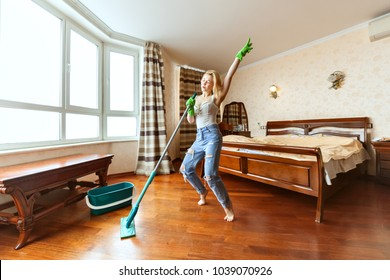 During the cleaning of the apartment, the woman sings and dances, in her hands a mop.