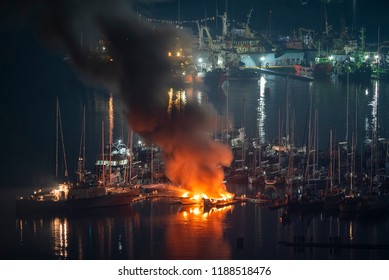 During the night, firefighters try to put out two luxury yachts that are catching fire at the marina berth