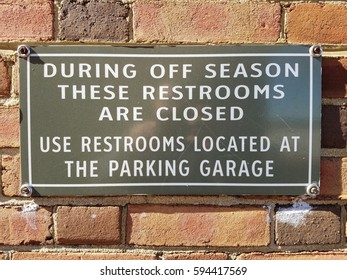 during off seasons restrooms are closed sign on brick wall