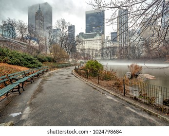 During a rain storm in Central park on the lake in winter with fog