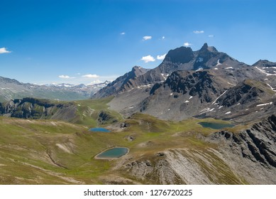 During a sunny summer day alpine landscape in the French Alps with three blue lakes, hiking trails between them and green pastures around, Vanoise National Park.