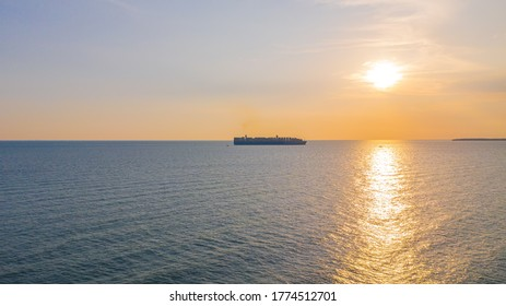 During sunset a Container cargo ship arriving in the harbor. Big container ship  enters the port of Klang at the Klang delta, Malaysia. The Klang port is located on the island Pulau Indah