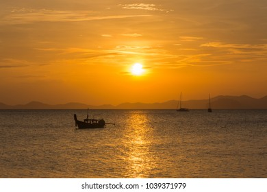 During a sunset or sunrise, boat in the water.