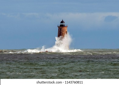During a unique high tide a huge wave wraps around the stone tower of Whaleback lighthouse in Maine.