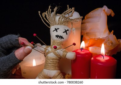 During a voodoo ceremony candles light up and a voodoo doll is stung with needles