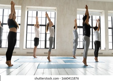 During yoga class seven multi-ethnic people performing Mountain asana or Tadasana Pose, side view full length. Exercise strengthens body, improves balance and posture. Healthy sporty lifestyle concept