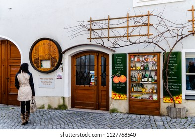 Durnstein, Wachau / Austria 01.03.2014: One of the small shops in town selling homemade products from region like vine. Woman passing by.