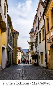 Durnstein, Wachau / Austria 01.03.2014: View at Street in Durnstein in early spring, Wachau valley, Austria. Tourist walking on narrow street of town.