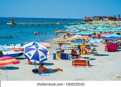 Durres, Albania, August 21, 2018: The main city beach near the waterfront. We see a calm azure sea, a sandy beach, many colorful umbrellas and beach chaise longue, a crowd of tourists and locals