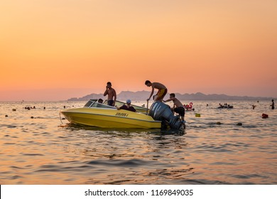 DURRES ALBANIA, AUGUST 5, 2018: Close sea view of orange and yellow sunset with people in a moored motorboat against the horizon in Durres Albania August 5, 2018. People bathing in the background.