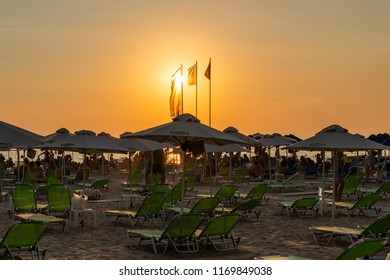 DURRES ALBANIA, AUGUST 5, 2018: Beautiful orange and yellow sunset view with people lying in sunchairs at a beach with sun umbrellas and flags in Durres Albania August 5, 2018.