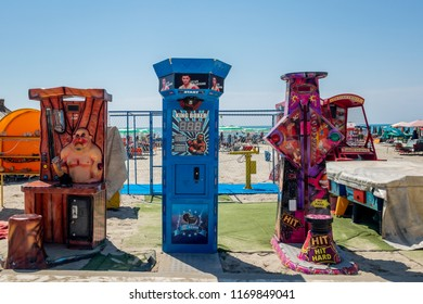 DURRES ALBANIA, AUGUST 5, 2018: Front view of three amusement park strength testing machines on the beach in Durres Albania August 5, 2018. Incidental people in the background.