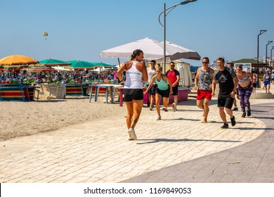 DURRES ALBANIA, AUGUST 5, 2018: Front view of a female instructor and group of people running at a beach path outdoors in Durres Albania August 5, 2018. Incidental people in the background.