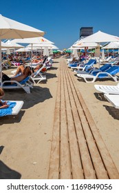 DURRES ALBANIA, AUGUST 5, 2018: Vertical perspective view of people lying in sunchairs sunbathing at a beach with a wooden boardwalk in Durres Albania August 5, 2018.