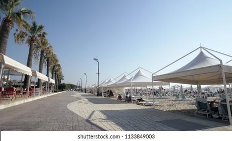 Durres, Albania - circa Aug, 2017: Touris walk pov on promenade seafront, beach,coast of beach resort in Durres, Golem, Albania