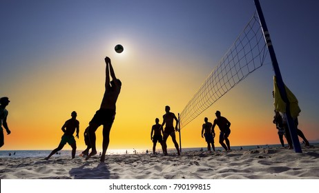 Durres, Albania - circa Aug, 2017: Silhouettes of young men playing volleyball on Varkala beach at sunset, Durres, Albania, SLOW MOTION