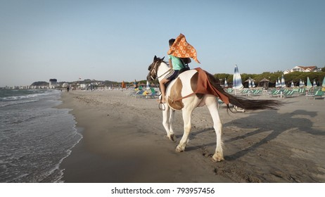 Durres, Albania - circa Aug, 2017: Boy riding horses at seaside on a sunny day. Horses galloping on the beach. Sport and travel concepts