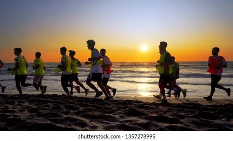 Durres, Albanie - circa Aug, 2017: The soccer team, coaching training running outdoor under the beach sunset, cinematic steadicam shot