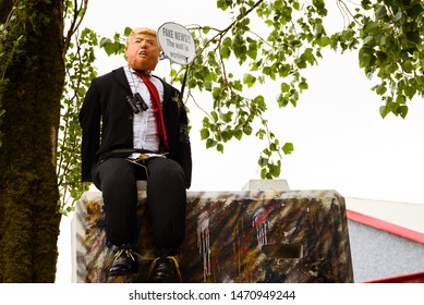 Durrow, Laois / Ireland - August 4, 2019: Scarecrow of Donald Trump seating over a wall at Durrow Scarecrow Festival