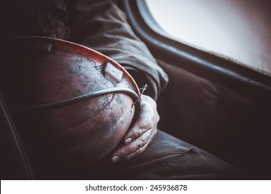 durty hands of miner worker hold helmet no face