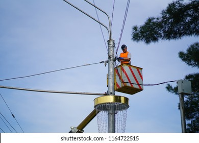 DUSHANBE, TAJIKISTAN - March 30, 2018: Man working on wires on a transmission pole.