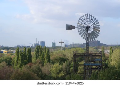 Dusiburg, NRW, Germany, 03/10/2018>  Old wind turbine in industrial area with industrial background. Old and new industry and commerce. Retail and manufacturing in juxtaposition. IKEA and power plants