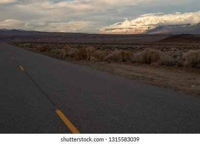 dusk clouds hang around snowy mountain range in distance across desert valley and rural road in California