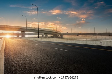 Dusk colored clouds in the background, highway overpass curved approach bridge