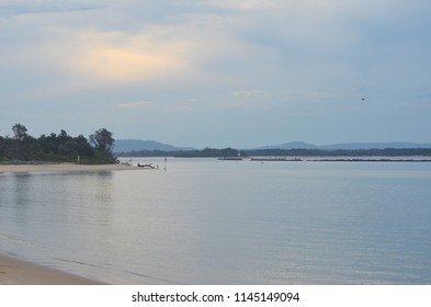 Dusk is falling over an inlet where a river flows to the sea. The sky is cloudy, and islands and rocks divide the inslet is into channels. Trees cover the foreshore. A man is fishing off the beach.