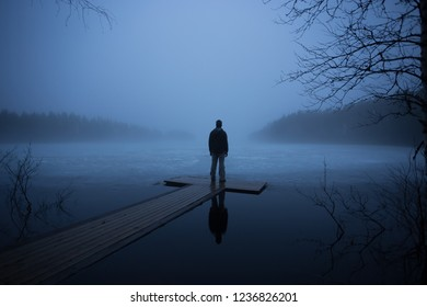 Dusk. Fog. A lone man looks at a frozen lake. Finnish spring.
