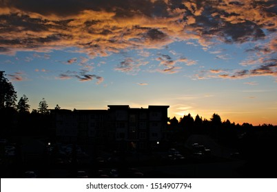Dusk moment view the end of a summer sunset storm clouds illumination by last rays of sunlight city skyline background