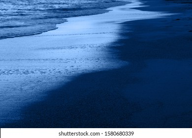 Dusk on the beach of the Mediterranean and mountains range on the horizon. Classic Blue Pantone 2020 year color in nature.