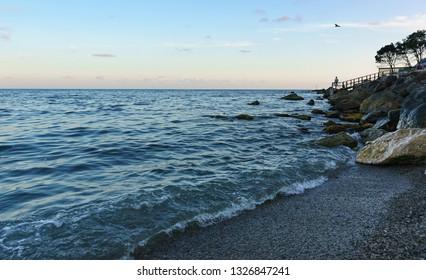 Dusk on the beautiful beach of Zelenyy Mys in Alupka. Calm evening sea in Crimea