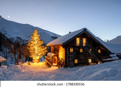 Dusk on a Holiday Hut in the Swiss Alps with Snow and Lighten up Tree