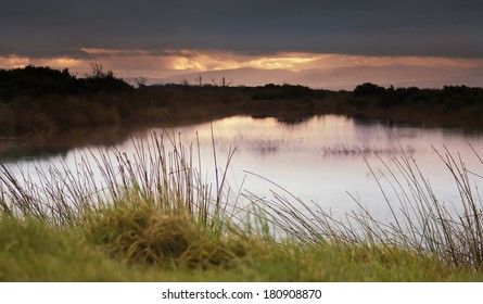 Dusk over a water channel at RSPB Mersehead Nature Reserve, Southwick, Dumfries and Galloway, Scotland, UK.