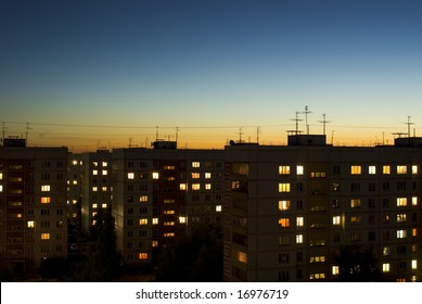 dusk sky and houses with lit windows background