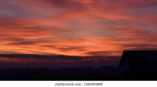 Dusk sunset silhouette with a building outline and an electricity pylon against bright red and orange clouds