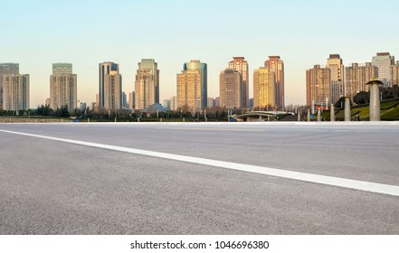 At dusk, Zhengzhou cityscape with asphalt road in the foreground