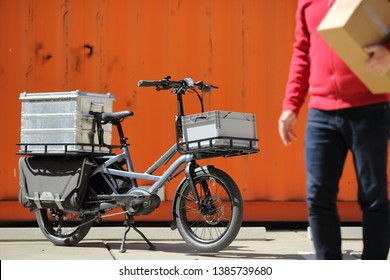 Dusseldorf / Germany – April 22, 2019: Cargo ebike and delivery man with boxes in front of an orange container on April 22, 2019 in Dusseldorf.